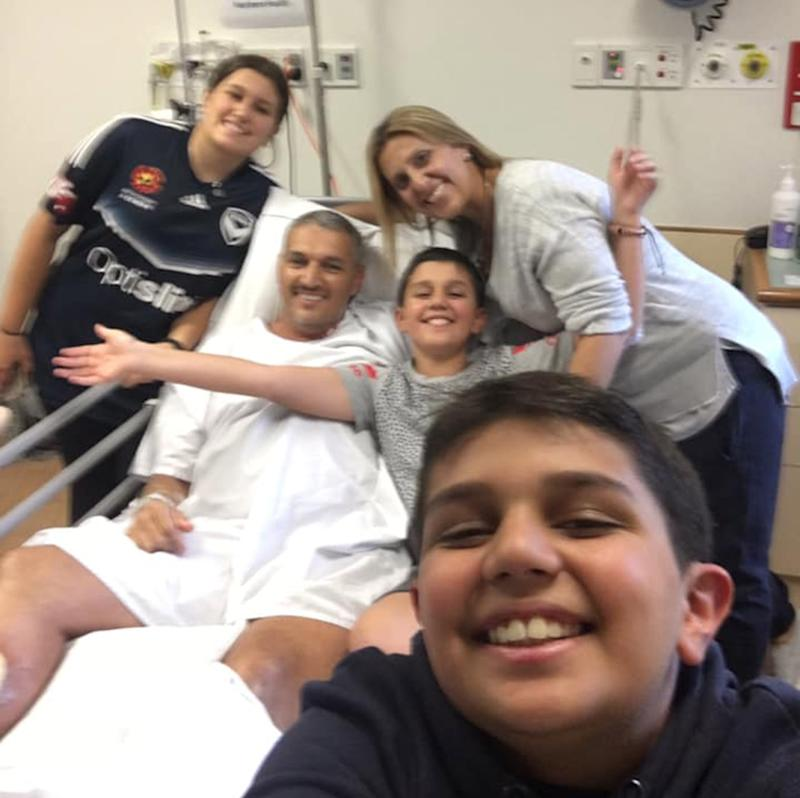 Pictured is Melbourne dad Adrian Nandapi in his hospital bed, supported by his family who are happy for his recovery from the flesh-eating bacteria..