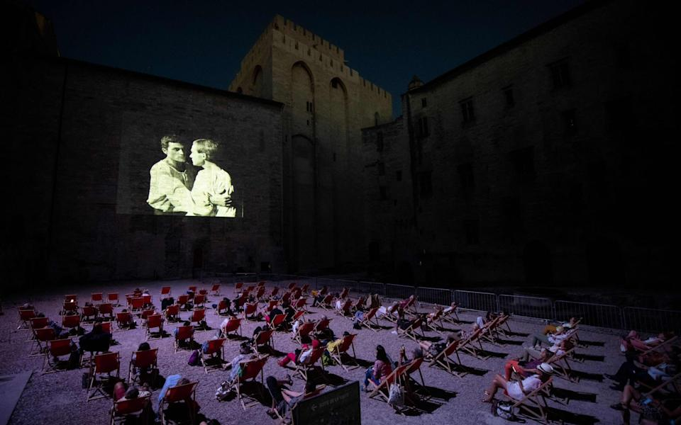 "People look at a video projection in the ""Cour d'Honneur du Palais des Papes"" in Avignon southern France. As the 2020 edition of the International Theatre Festival of Since Avignon theatre festival has been cancelled due to the COVID-19, coronavirus crisis, the festival's organization has decided to offer a cycle of video projection of plays that made its history - CLEMENT MAHOUDEAU / AFP"