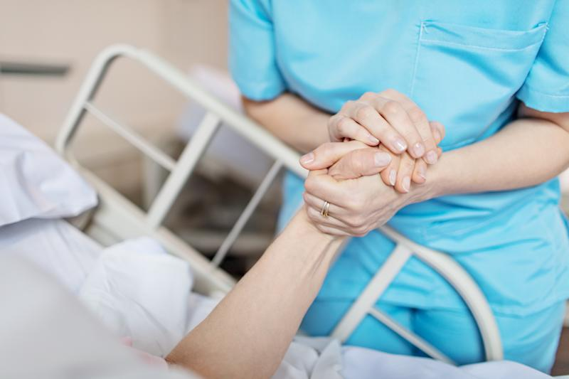 A female nurse is pictured holding senior woman's hand.