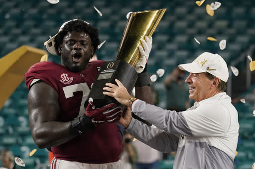 Alabama head coach Nick Saban and offensive lineman Alex Leatherwood hold the trophy after their win against Ohio State in an NCAA College Football Playoff national championship game, Tuesday, Jan. 12, 2021, in Miami Gardens, Fla. Alabama won 52-24. (AP Photo/Lynne Sladky)
