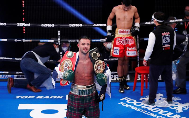 Josh Taylor poses with his belts after winning the fight against Apinun Khongsong. - REUTERS