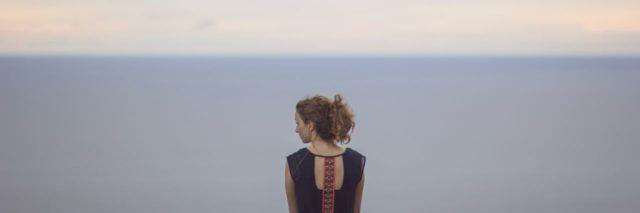 woman looking to the side, in front of the sky and water