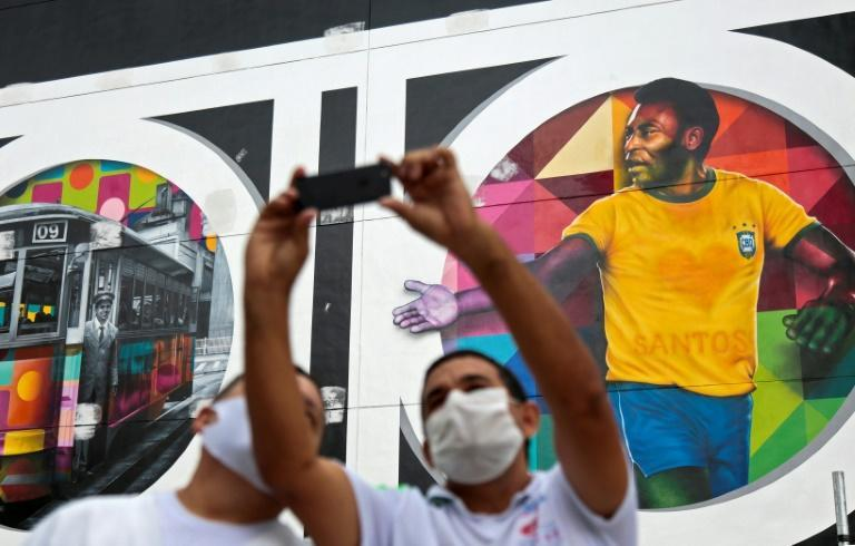 Fans pose for selfies next to a mural in Santos, Sao Paulo state, Brazil by Brazilian artist Kobra depicting Pele in his heyday