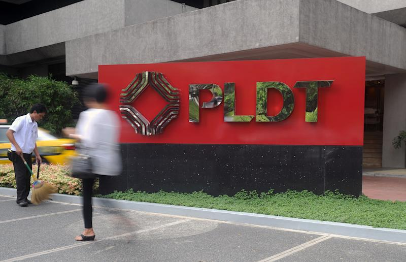 FILE PHOTO: A pedestrian walks past the Philippine Long Distance Telephone (PLDT) logo in Manila's financial district. (Photo: JAY DIRECTO/AFP via Getty Images)