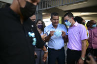 """FILE - In this March 10, 2021 file photo, Puerto Rico Gov. Pedro Pierluisi, center, attends a mass vaccination campaign against COVID-19 at the Maria Simmons elementary school in Vieques, Puerto Rico. Pierluisi has resisted tighter restrictions, saying another lockdown would be too extreme and that things will keep improving and the island could achieve herd immunity by August 2021: """"The solution is vaccination."""" (AP Photo/Carlos Giusti, File)"""