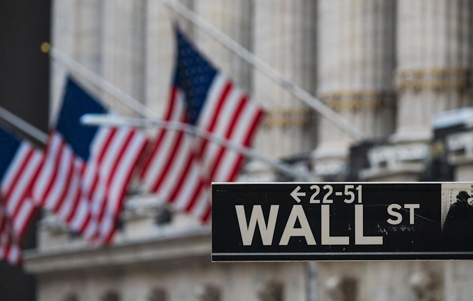 A Wall St sign hangs at the New York Stock Exchange (NYSE) at Wall Street on March 23, 2021 in New York City. - Wall Street stocks were under pressure early ahead of congressional testimony from Federal Reserve Chief Jerome Powell as US Treasury bond yields continued to retreat. (Photo by Angela Weiss / AFP) (Photo by ANGELA WEISS/AFP via Getty Images)