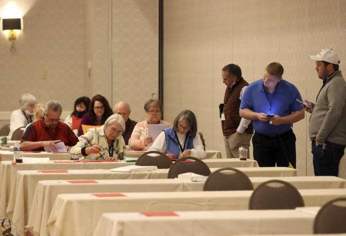 Tellers, sitting, work on counting ballots next to observers for the Virginia Republican Party primary at Richmond Marriott in Richmond, Va., on Sunday, May 9, 2021. (Daniel Sangjib Min/Richmond Times-Dispatch via AP)