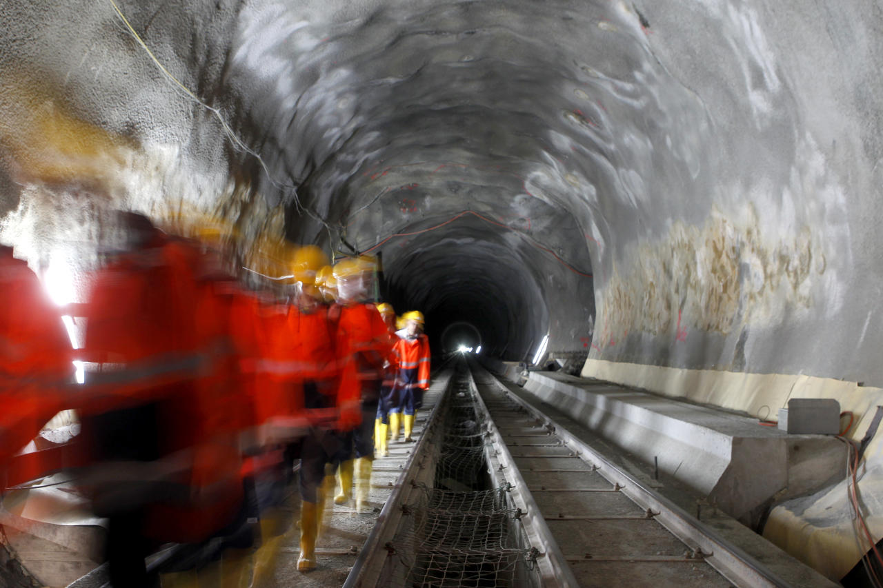 Visitors walk through the construction site of the NEAT Gotthard Base Tunnel at the Erstfeld-Amsteg section October 5, 2010. With a length of 57 km (35 miles) crossing the Alps, the world's longest train tunnel should become operational at the end of 2017.   REUTERS/Arnd Wiegmann (SWITZERLAND - Tags: BUSINESS CONSTRUCTION TRANSPORT TRAVEL) - RTXT2QF