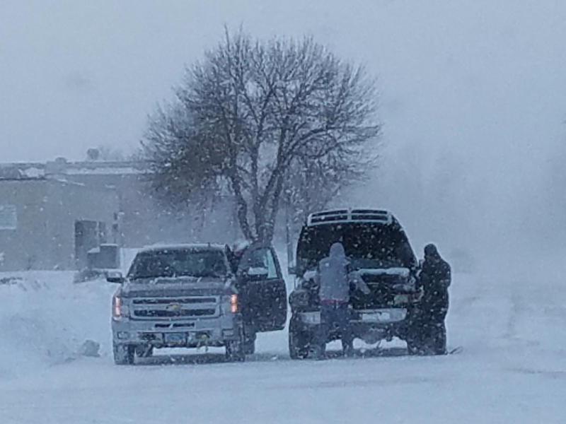Residents in Fargo, N.D., attempt to jump-start a vehicle with a dead battery in the middle of a snowstorm on Saturday, Jan. 18, 2020. A blizzard warning was issued until Saturday evening for parts of North Dakota, South Dakota, Minnesota and Iowa as wind gusts approaching 50 mph made travel impossible in open areas and even difficult in the cities. Two roads in the city limits of Fargo remained closed because of low visibility and snow drifts. (Jim Monk/KFGO Radio, Fargo via AP)