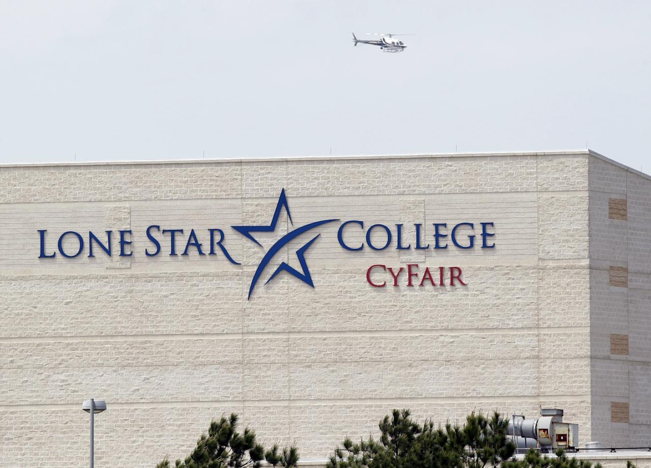 A police helicopter circles above the Cy-Fair campus of Lone Star Community College in Cypress, Texas, where officials say about a dozen people have been wounded in a stabbing attack Tuesday, April 9, 2013. The Harris County Sheriff's department confirmed at least 11 people wounded and that authorities have one suspect in custody. (AP Photo/Houston Chronicle, Melissa Phillip)