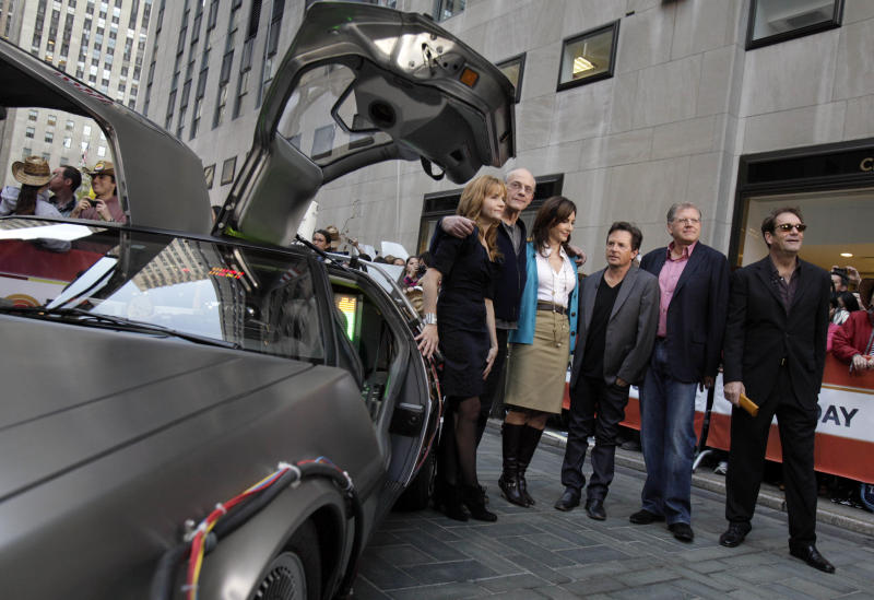"Cast members of the ""Back to the Future"" movies appear on the NBC ""Today"" television program, commemorating the 25th anniversary of the films, in New York Tuesday, Oct. 26, 2010. They are, from left, posing with a replica of the DeLorean car, Lea Thompson, Christopher Lloyd, Mary Steenburgen, Michael J. Fox, director Robert Zemeckis , and Huey Lewis. (AP Photo/Richard Drew)"