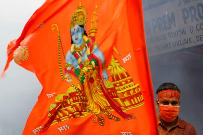 A man stands near a flag during a live screening of the stone laying ceremony of the Ram Temple by Prime Minister Narendra Modi in Ayodhya, in New Delhi