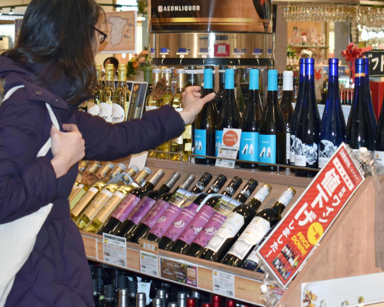 A customer picks up a bottle of wine imported from Spain after being priced down at a retail store in Chiba, near Tokyo, Friday, Feb. 1, 2019. The European Union and Japan have inaugurated a landmark deal they say will boost trade between the two economic powers and sends the message that international agreements still have a purpose in an age of increasing protectionism. The agreement that comes into effect Friday will scrap nearly all tariffs on products both sides trade in. (Kyodo News via AP)