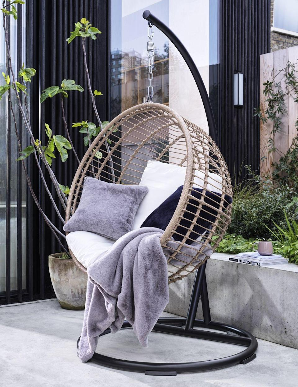 """<p>Who says <a href=""""https://www.housebeautiful.com/uk/garden/g35548498/hanging-egg-chair/"""" rel=""""nofollow noopener"""" target=""""_blank"""" data-ylk=""""slk:hanging egg chairs"""" class=""""link rapid-noclick-resp"""">hanging egg chairs</a> are just for summer? According to Habitat's trend report, they're here to stay — even if we need a blanket or two to enjoy them fully. </p><p>'Our hanging wicker chair plays into the popular trend for cocoon-like designs that provide a cosy nook to relax and wind down,' says Rachael Fell, Furniture Buying Manager.</p><p>'We've reworked the classic egg chair shape with a circular design, incorporating a rattan effect as a nod to nature and escapism. It can be easily moved indoors if you're up against rain or snow when craving that me-time moment.'</p>"""