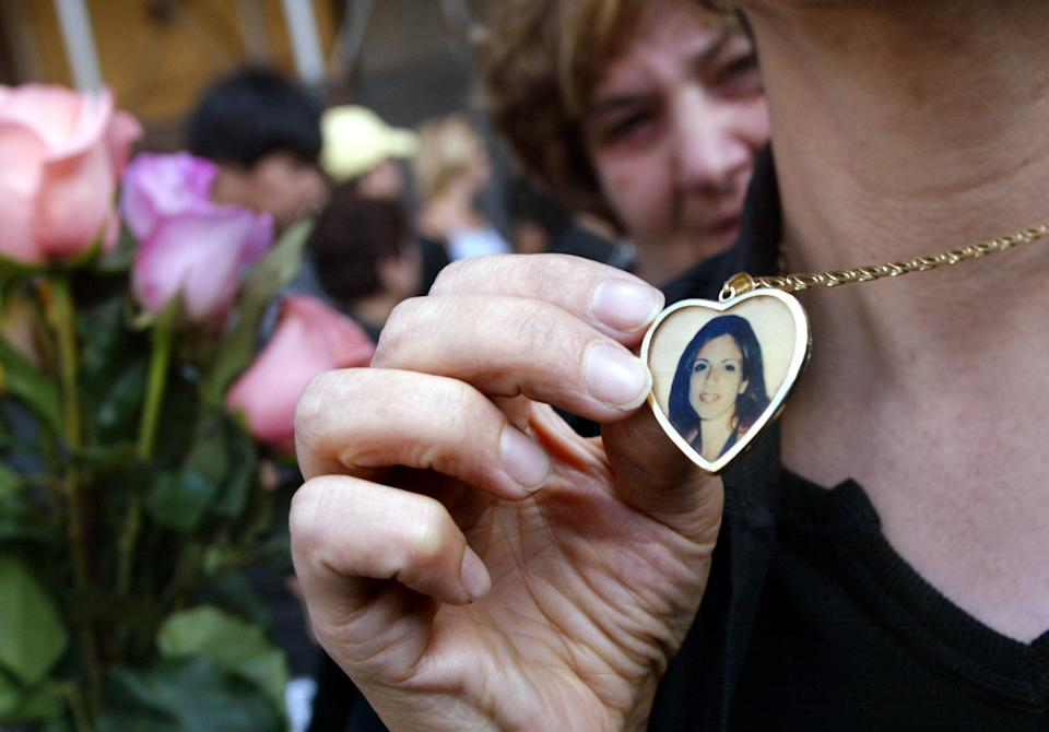 NEW YORK - SEPTEMBER 11:   A relative wears a necklace near Ground Zero with a picture of Daniela Notaro, killed in the World Trade Center attacks a year ago, September 11, 2002 in New York City.  (Photo by Mario Tama/Gettty Images)