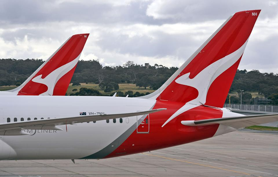 """Two Qantas planes are seen at at Melbourne Airport on August 20, 2020. - Australian flag carrier Qantas on August 20, 2020 posted an almost 2 billion USD annual loss after a """"near-total collapse"""" in demand due to the COVID-19 coronavirus pandemic. (Photo by William WEST / AFP) (Photo by WILLIAM WEST/AFP via Getty Images)"""