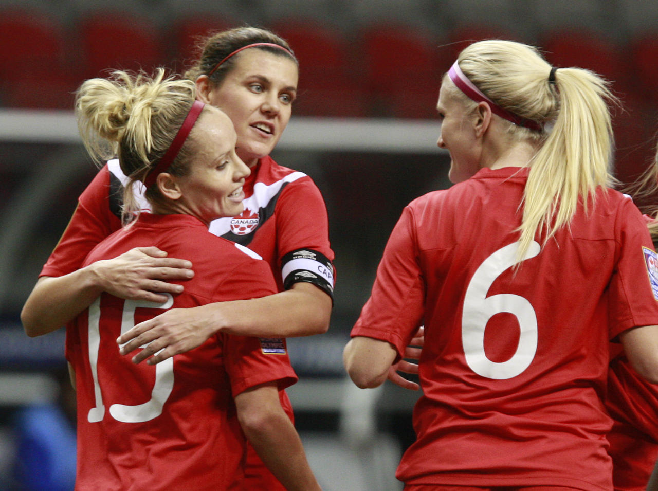 VANCOUVER, CANADA - JANUARY 19:  Christine Sinclair #12 and Kaylyn Kyle #6 of Canada congratulate goal scorer Kelly Parker #15 of Canada during a 6-0 win over Haiti to open the 2012 CONCACAF Women's Olympic Qualifying Tournament at BC Place on January 19, 2012 in Vancouver, British Columbia, Canada.  (Photo by Jeff Vinnick/Getty Images)