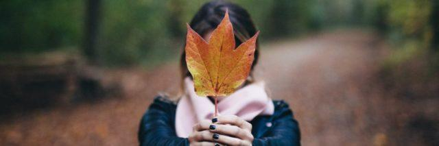 photo of woman holding up autumn fall leaf covering her face