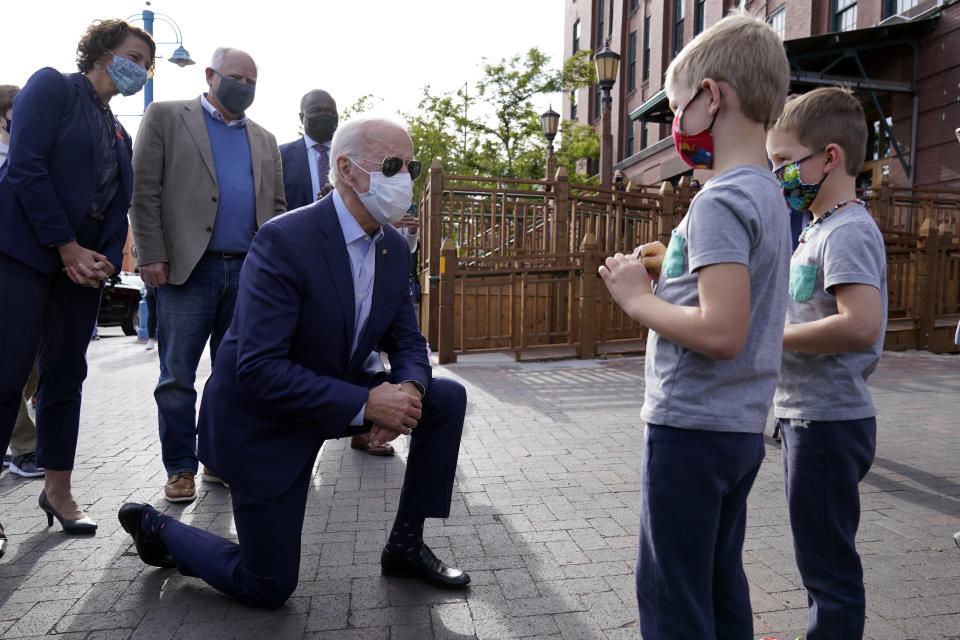 Democratic presidential candidate former Vice President Joe Biden talks to two boys as leaves the Amazing Grace Bakery & Cafe in Duluth, Minn., Friday, Sept. 18, 2020, with the Mayor of Duluth Emily Larson, left, and Minnesota Mayor Tim Walz, center. (AP Photo/Carolyn Kaster)
