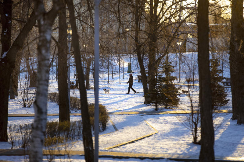 A woman walks her dog through an empty boulevard during a frosty morning in Moscow, Russia, Wednesday, April 1, 2020. The Russian capital has woken up to a lockdown obliging most people in the city of 13 million to stay home. The government ordered other regions of the vast country to quickly prepare for the same as Moscow, to stem the spread of the new coronavirus. The new coronavirus causes mild or moderate symptoms for most people, but for some, especially older adults and people with existing health problems, it can cause more severe illness or death. (AP Photo/Alexander Zemlianichenko)