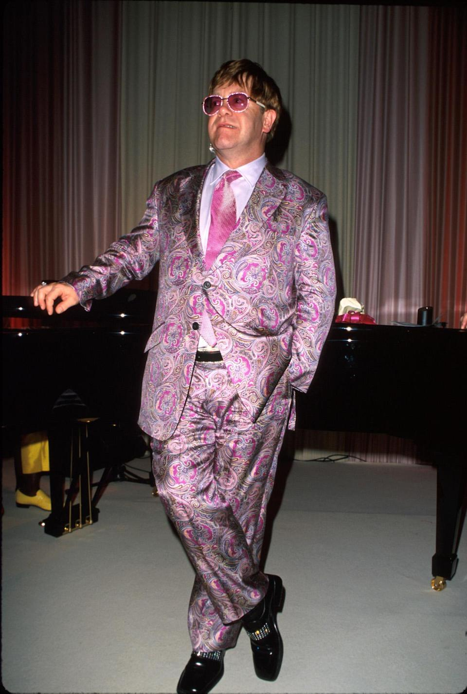 <p>Elton John in a pink-and-purple paisley silk suit with a bright pink tie in 2000. (Photo: Getty Images) </p>