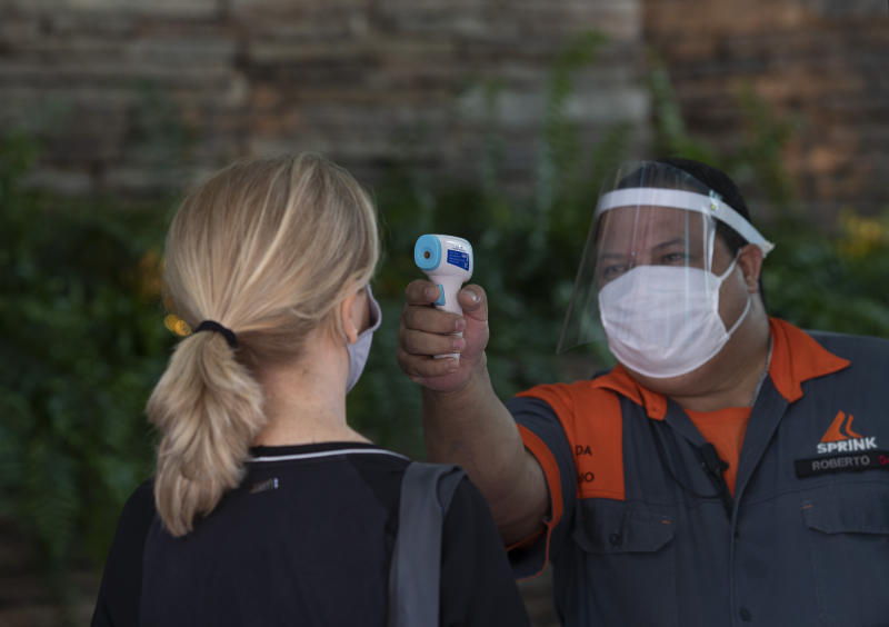 A vendor stands still as her temperature is measured at the entrance of a shopping mall amid the new coronavirus pandemic, in the Botafogo neighborhood of Rio de Janeiro, Brazil, Thursday, June 11, 2020. Rio is easing restrictive quarantine measures, and on Thursday allowed shopping centers to open as long as they observed preventive measures. (AP Photo/Silvia Izquierdo)