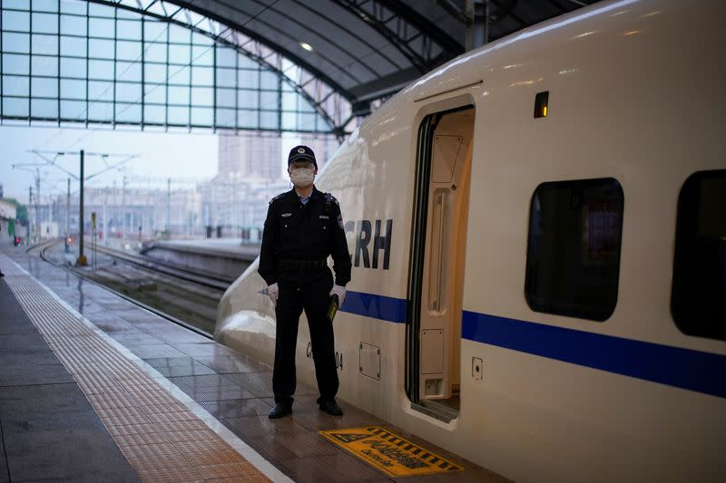 A policeman stands beside a high-speed train, which is the first train to leave Hankou Railway Station in Wuhan