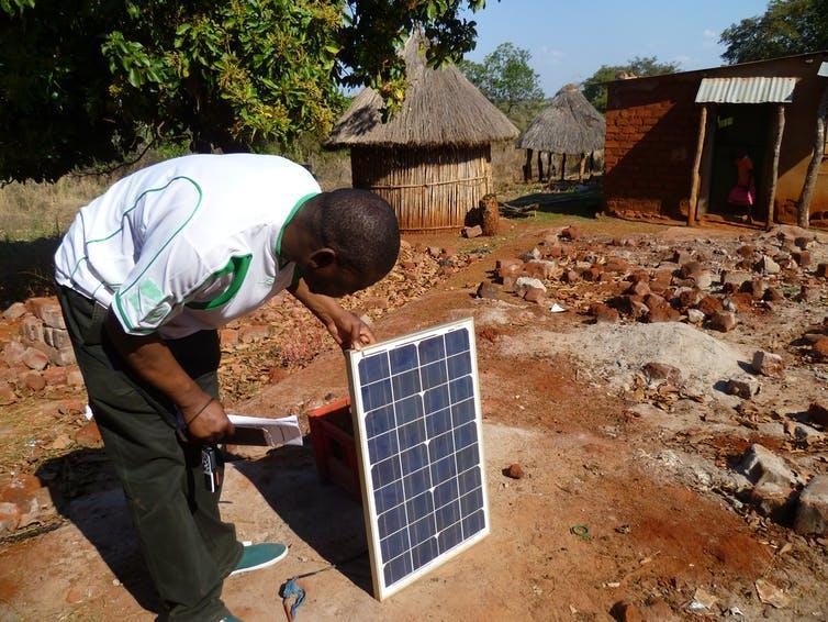 A person inspects a solar panel