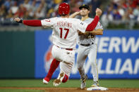 Pittsburgh Pirates second baseman Adam Frazier, rear, throws to first after forcing out Philadelphia Phillies' Rhys Hoskins at second on a double play hit into by J.T. Realmuto during the third inning of a baseball game Tuesday, Aug. 27, 2019, in Philadelphia.. (AP Photo/Matt Slocum)
