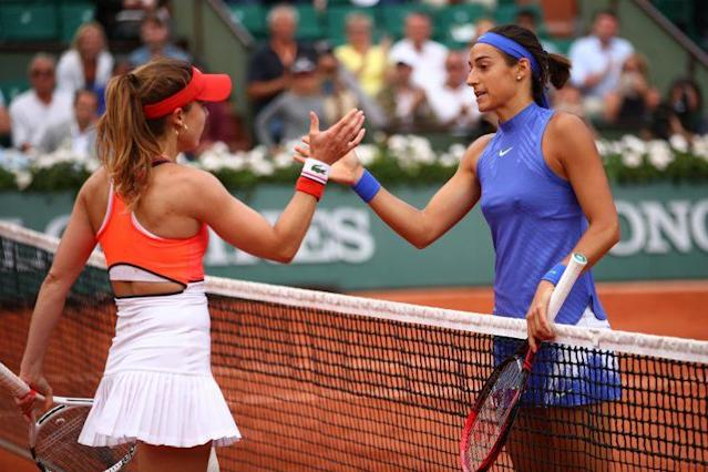 """<a class=""""link rapid-noclick-resp"""" href=""""/olympics/rio-2016/a/1085261/"""" data-ylk=""""slk:Caroline Garcia"""">Caroline Garcia</a> (blue) shakes hands with fellow French player <a class=""""link rapid-noclick-resp"""" href=""""/olympics/rio-2016/a/1085259/"""" data-ylk=""""slk:Alize Cornet"""">Alize Cornet</a> (orange) after their match. (Getty Images)"""