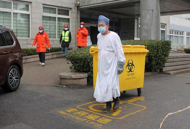 An employee at the Beijing Chaoyang An'yuan Hospital disposes of medical waste on 14 February. (Getty Images)