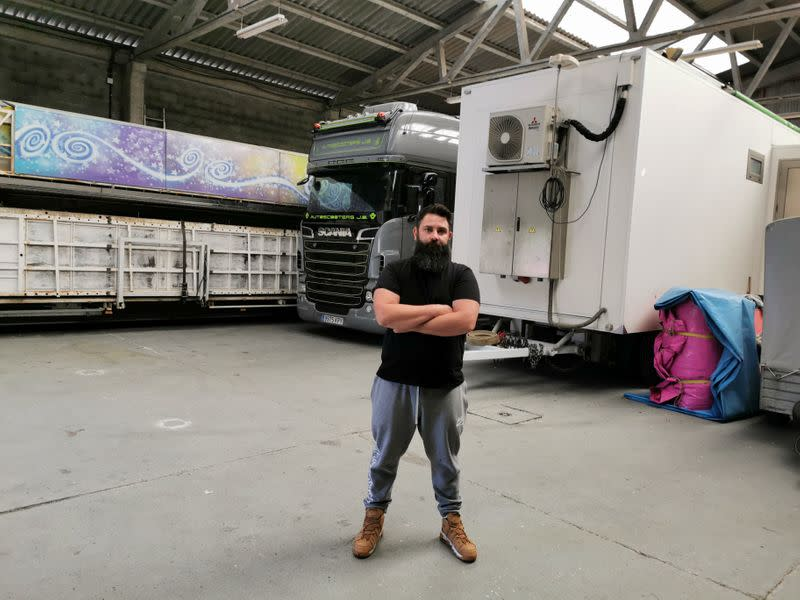 Juan Balsa poses in front of their trucks in a warehouse, amid the coronavirus disease (COVID-19) outbreak, in Carnoedo