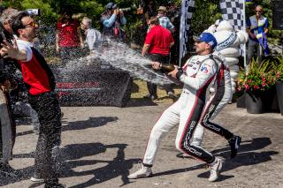 <em>Earl Bamber celebrates with team members after winning the GTLM class of the IMSA race July 7, 2019 at Canadian Tire Motorsport Park (Brian Cleary/Getty Images).</em>