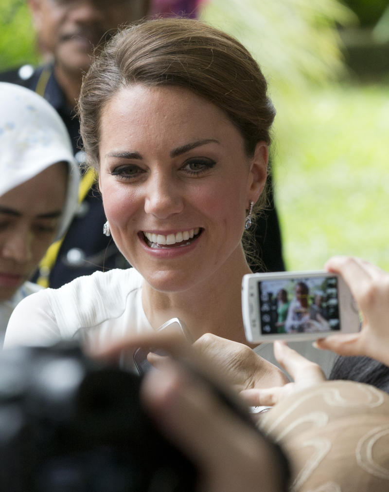 Kate, the Duchess of Cambridge shakes hands with well-wishers during a walk through a central city park in Kuala Lumpur, Malaysia, Friday, Sept. 14, 2012. Prince William and Kate are on a nine-day tour of the Far East and South Pacific in celebration of Queen Elizabeth II's Diamond Jubilee. (AP Photo/Mark Baker)