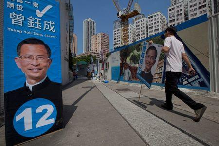A supporter of candidate Tsang Yok-sing, from the pro-Beijing 'Democratic Alliance for the Betterment and Progress of Hong Kong' carries a placard of Yok-sing on election day for the Legislative Council in Hong Kong