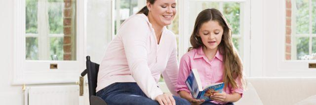 Mother sitting in her wheelchair helping daughter read book