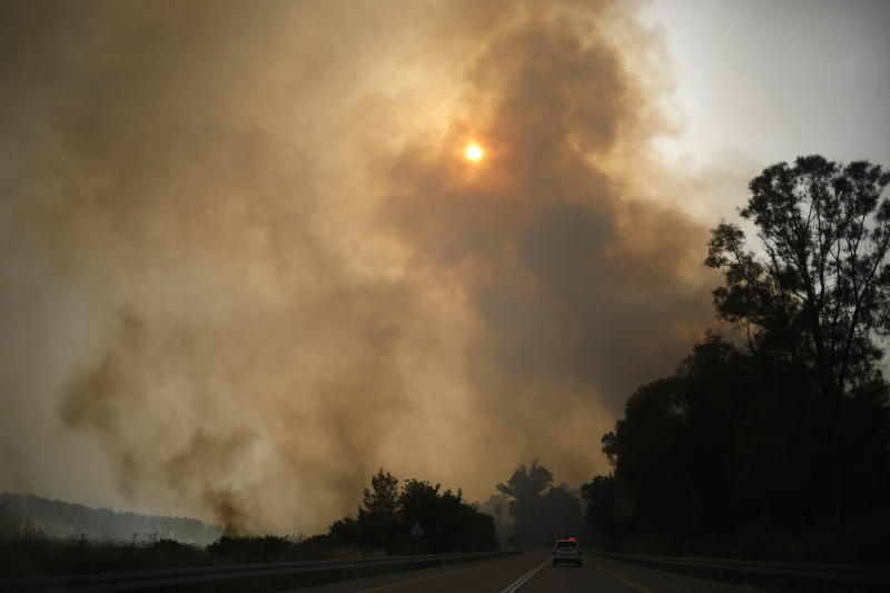 Smoke rises as a wildfire rages near Kibbutz Harel, Israel, Thursday, May 23, 2019. Israeli police have ordered the evacuation of several communities in southern and central Israel as wildfires rage amid a major heatwave. (AP Photo/Ariel Schalit)