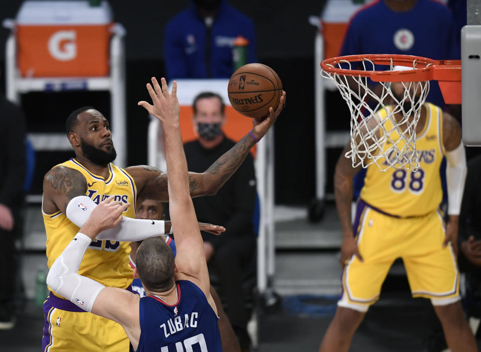 LeBron James #23 of the Los Angeles Lakers scores on a layup over Ivica Zubac #40 of the LA Clippers during a 116-109 LA Clippers win in the season opening game.