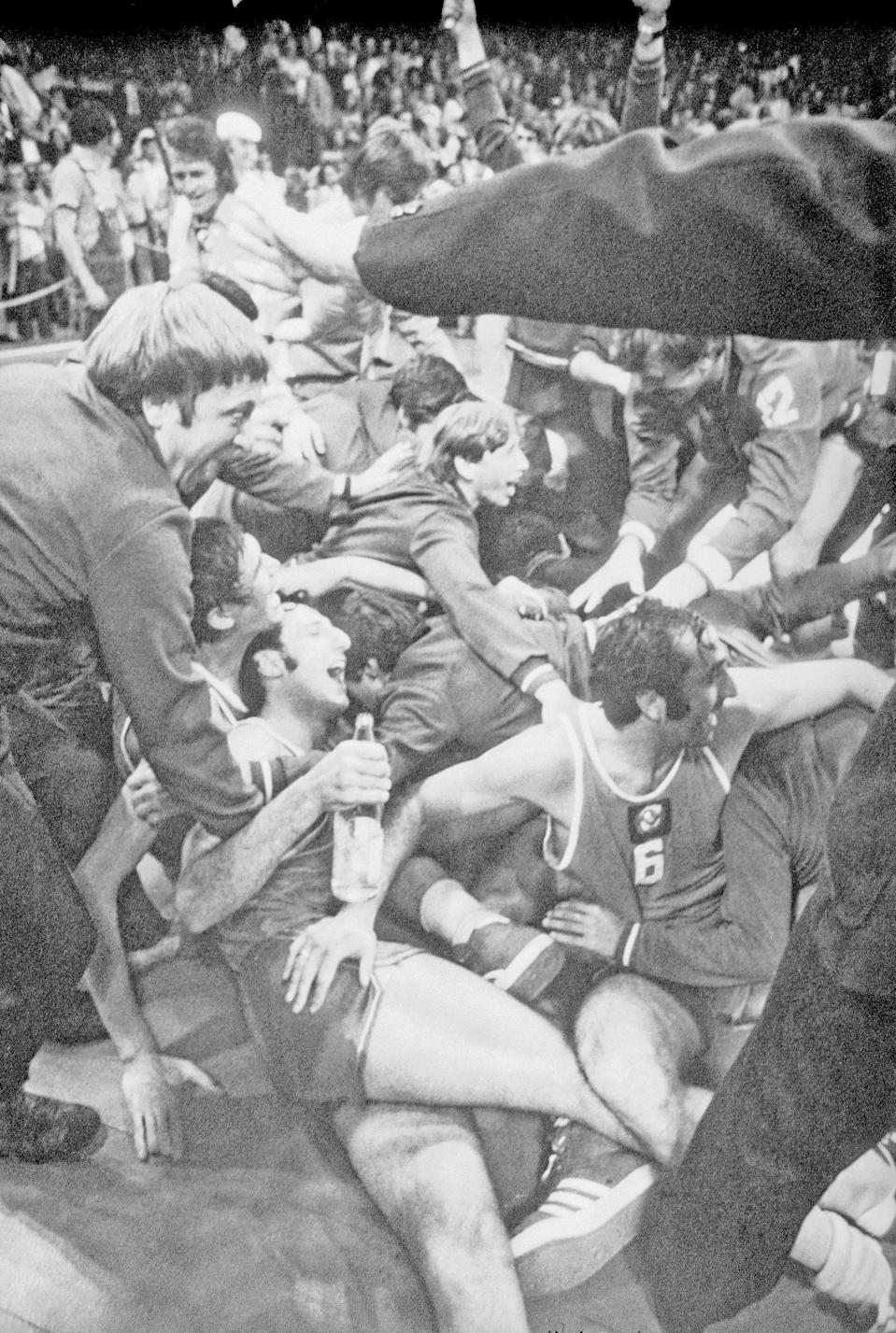 FILE - In this Sept. 10, 1972, file photo, Soviet players and supporters join in a joyous melee on the floor of the Munich Basketball Stadium, in Munich, after the Soviet team scored a 51-50 victory over the United States in the gold medal game of the Olympic basketball tournament. (AP Photo/File)