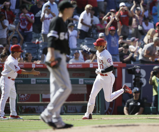 Los Angeles Angels third base coach Mike Gallego, back left, reaches to congratulate designated hitter Shohei Ohtani, right, who hit a two-run home run off Chicago White Sox's Ross Detwiler, center, during the seventh inning of a baseball game in Anaheim, Calif., Sunday, Aug. 18, 2019. (AP Photo/Alex Gallardo)