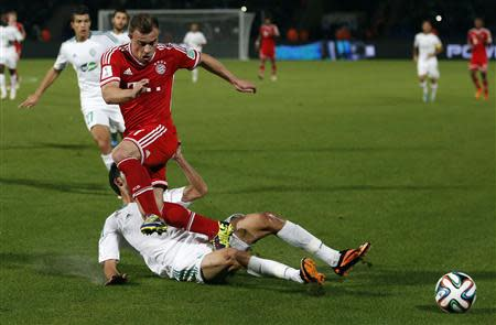 Xherdan Shaqiri of Germany's Bayern Munich trips over Mohamed Oulhaj (bottom) of Morocco's Raja Casablanca during their 2013 FIFA Club World Cup final match at Marrakech stadium December 21, 2013. REUTERS/Youssef Boudlal