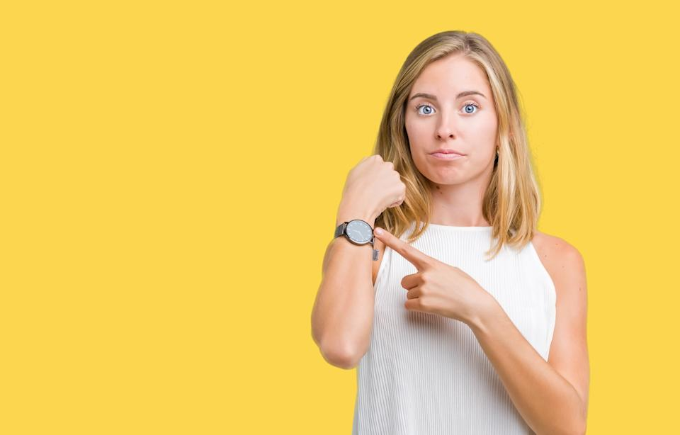 Beautiful young elegant woman over isolated background In hurry pointing to watch time, impatience, upset and angry for deadline delay