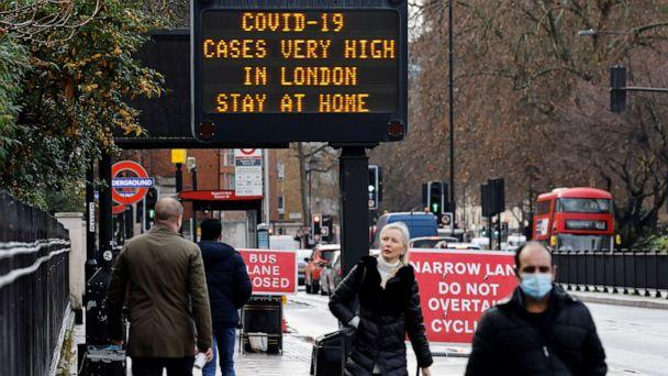 PHOTO: Pedestrians walk past a sign alerting people about high numbers of COVID-19 cases in central London on Dec. 23, 2020. (Tolga Akmen/AFP via Getty Images)