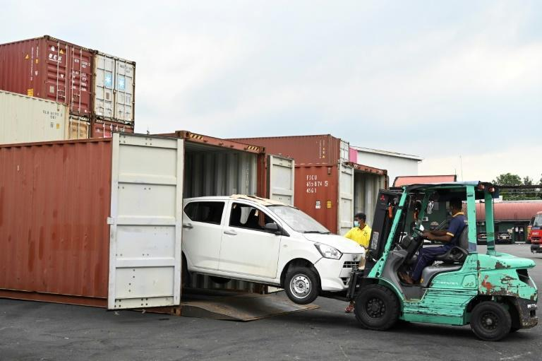 Workers unload illegally imported vehicles at a warehouse in Colombo