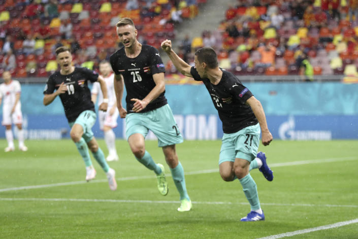 Austria's Stefan Lainer, right, celebrates after scoring his side's first goal during the Euro 2020 soccer championship group C match between Austria and North Macedonia at the National Arena stadium in Bucharest, Romania, Sunday, June 13, 2021. (Marko Djurica/Pool via AP)