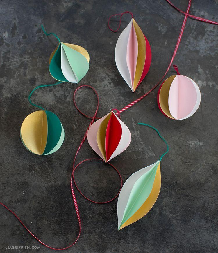 """<p>These are super simple to make, but the shapes and colors will pop on your tree. Gather colored paper, thread, and glue for this one.</p><p>Get the tutorial at <a href=""""https://liagriffith.com/colorful-3d-papercut-ornaments/"""" rel=""""nofollow noopener"""" target=""""_blank"""" data-ylk=""""slk:Lia Griffith"""" class=""""link rapid-noclick-resp"""">Lia Griffith</a>.</p>"""