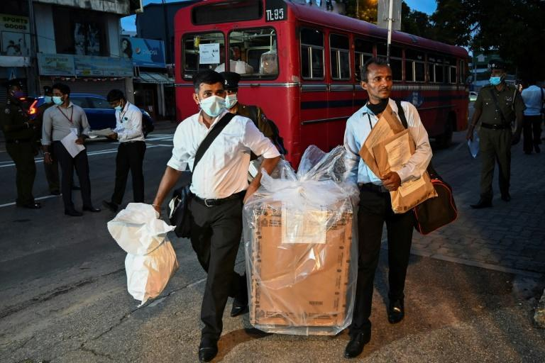 Sri Lankan election officials take a ballot box to a counting centre after the parliamentary election voting sites closed