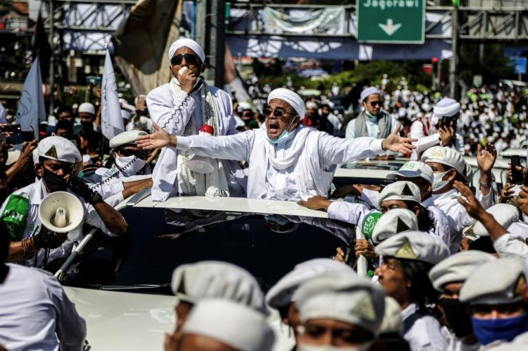 Islamic Defender's Front leader Rizieq Shihab stretches out his arms as he arrives to inaugurate a mosque in Bogor in November 2020