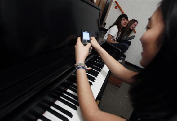 Hee-hyeon Han (R) from South Korea takes a break from her piano practice to send text messages as Tina Chuang, from Pingtung, Taiwan (C) and Lena Kraft, from Munich, Germany share a laugh in a small room after hours at Grant-Deuel School in Revillo, South Dakota February 13, 2012.
