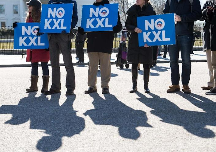 Demonstrators hold signs against the proposed Keystone XL pipeline from Canada to the Gulf of Mexico in front of the White House in Washington, DC, on January 28, 2015 (AFP Photo/Nicholas Kamm)